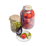Pickled cucumbers and tomato on saucer and in glass jars Royalty Free Stock Photography