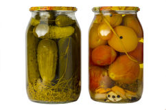 Pickled cucumbers and tomatoes in jars. Salted cucumbers and tomatoes in homemade salted cans on white background Stock Image