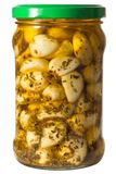Pickled garlic in a jar of green marjoram Royalty Free Stock Photography