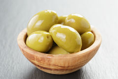 Pickled giant green olives in olive bowl on slate Stock Photo