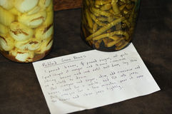 Pickled Green Beans. A recipe card with a handwritten recipe for pickled green beans and a jar full of them next to a jar of pickled eggs Royalty Free Stock Images
