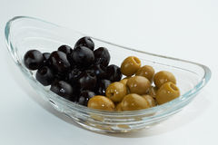 Pickled green and black olives in a glass bowl on white background Stock Image