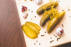 Pickled green cucumbers, fresh garlic and spices on a wooden board stock photo