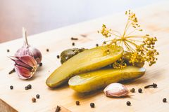 Pickled green cucumbers, garlic and spices on a wooden board royalty free stock image