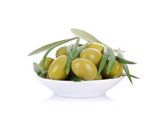 Pickled green olives in a bowl and olive tree branch Stock Images