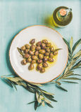 Pickled green olives, olive tree branch, virgin oil, blue background Royalty Free Stock Photo