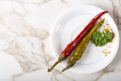 Pickled green and red pepperoni pepper in plate with parsley Stock Image
