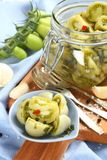 Pickled green tomatoes in blue bowl and in glass jar Stock Photos