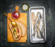 Pickled herring fish sandwiches with red onion sauce on old cutting board , top view Royalty Free Stock Image