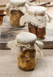 Pickled mushrooms in transparent glass jar Stock Photos