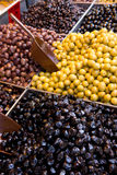 Pickled olives on market stall. Different colored pickled olives on market stall for sale Royalty Free Stock Photography