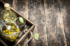 Pickled olives with oil and spices on an old tray. On a wooden background Stock Images