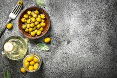 Pickled olives with olive oil. On a rustic background Stock Photos