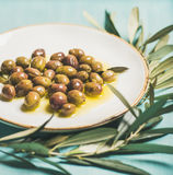 Pickled olives on plate and olive-tree branch over blue background. Pickled green Mediterranean olives in virgin oil on white ceramic plate and green olive tree Stock Photo
