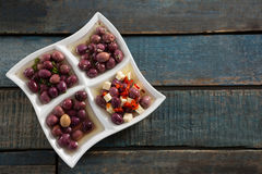 Pickled olives in platter. On wooden table Stock Photos
