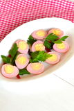 Pickled peeled hard-boiled quail eggs, stained pink by grated beet Stock Photo