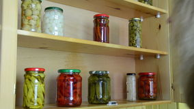 Pickled pepper tomato jar. Woman puts jars with pickled red peppers and tomatoes in a kitchen cupboard shelves stock video