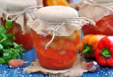 Pickled peppers in tomato juice with onions, garlic and basil. Stock Photography