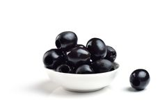 Pickled pitted black olives. In a bowl isolated on a white background Royalty Free Stock Photos