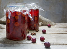 Pickled plums with spices in two glasses on a rustic wooden tabl Stock Images