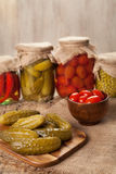 Pickled preserved vegetables in jars, cucumbers, pepper, tomatoes and peas Royalty Free Stock Photo