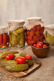 Pickled preserved vegetables in jars, cucumbers, pepper, tomatoes and peas Royalty Free Stock Image