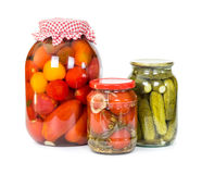 Pickled tomatoes and cucumbers in glass jars Royalty Free Stock Images