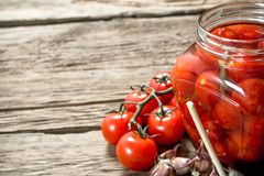 Pickled tomatoes in a glass jar with garlic and herbs stock image