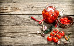 Pickled tomatoes in a glass jar with garlic and herbs stock photography