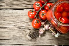 Pickled tomatoes in a glass jar with garlic and herbs royalty free stock photo