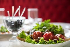 Pickled tomatoes with napa cabbage leaves and other greens on festive table in the restaurant. Catering service in Ukraine restaur. Pickled tomatoes with napa stock photo