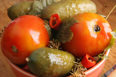 Pickled vegetables. Pickled tomatoes and cucumbers in the plate Royalty Free Stock Images