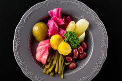 Pickled vegetables in iron plate on black background. Garlic, wild leek, bush pumpkin, herbs, cucumber, cabbage, bean. Top view Royalty Free Stock Photos
