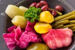 Pickled vegetables in iron plate close up. Garlic, wild leek, bush pumpkin, herbs, cucumber, cabbage, bean. Selective focus. Pickled vegetables in iron plate Stock Photos
