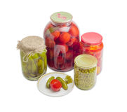 Pickled vegetables on saucer and in glass jars Stock Photo
