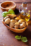 Pickled white mushrooms in wooden bowl Stock Images