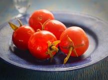 Pickledwith-Vorlage würzt Tomaten auf einer blauen Platte Stockbilder