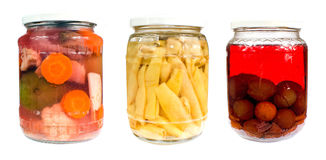 Pickles. Jars of assorted pickles: Sour green tomatoes and cauliflower, yellow string beans and cherry plums Royalty Free Stock Photography