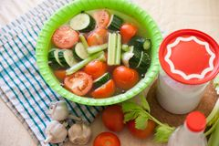 Pickling cucumbers and tomatoes. Pickled vegetables with brine in green plate royalty free stock photography