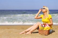 Picknick auf dem Strand Blonde junge Frau mit Korb des Lebensmittels Lizenzfreies Stockfoto