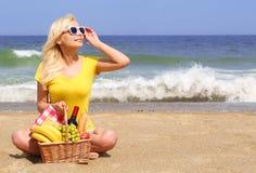 Picknick auf dem Strand Glückliche blonde junge Frau Stockbilder