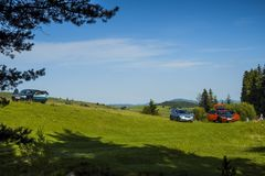 Picknick, auto's in een opheldering in de bergen die op green worden geparkeerd stock foto's
