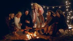 Picknick, bedrijf van jongerengebraden gerecht banger op vuur bij nacht op dijk stock video