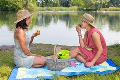 Picknick de deux femmes sur le côté de l'eau Image libre de droits