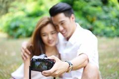 Picknick der glücklichen Datierungspaare im Freien mit Kamera lizenzfreie stockbilder