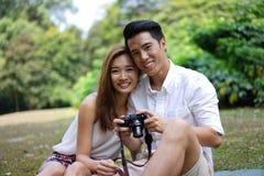 Picknick der glücklichen Datierungspaare im Freien mit Kamera lizenzfreies stockfoto
