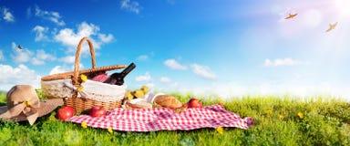 Picknick - Korb mit Brot und Wein auf Wiese Stockfotografie