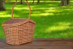 Picknick-Korb oder Fessel auf Holzbank im Park Lizenzfreie Stockbilder