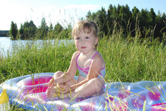 Picknick. Liten flickasammanträde på gräset nära sjön Arkivbilder