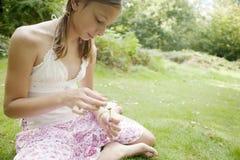 Picknick-Mädchen, das Blumenblätter von einer Gänseblümchen-Blume abzieht. Stockfotografie